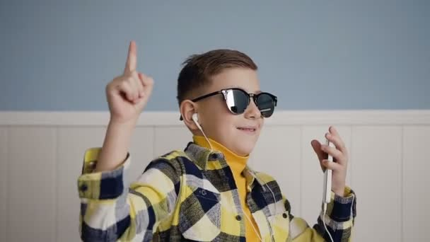 A handsome guy in sunglasses listens to music from the phone in white headphones and he fun dancing in the white background at home. Indoors. Technology