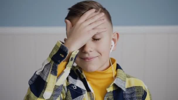 Portrét tváře okouzlující chlapec blondýnka s modrýma očima, kdo poslouchá hudbu ve sluchátkách se dívá na kameru obaluje vlasy s jeho ruku a usmívá se. Detailní záběr