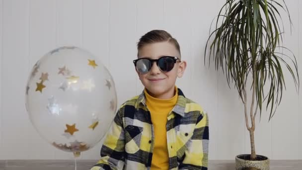 A handsome little boy in sunglasses sits on the floor against the background of a white wall and holds a balloon