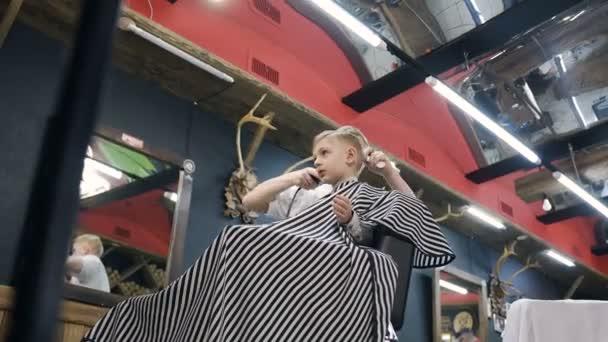 Barber zastřihne vlasy její malý klienta s nůžkami. Hlavní stacky vlasy Fén chlapce v holičství, kadeřnice dělá účes pro malého chlapce