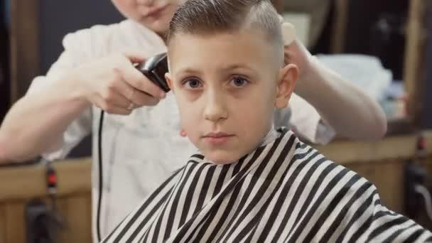Un Ragazzo Sveglio Che Si Siede Su Una Sedia In Un Look Da Saloni Di Parrucchiere Nella Fotocamera E Dimostra Con La Sua Mano Che Tutto Va Bene E Gli Piace Il Suo Barbiere E Un Nuovo Taglio Di