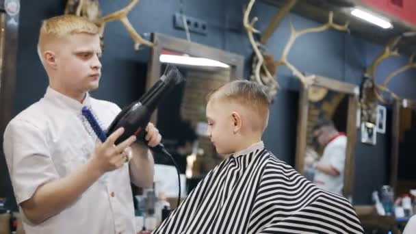 Barber dries hair the little boy in hairdressing salon. Little beautiful boy getting haircut by barber while sitting In chair at barbershop