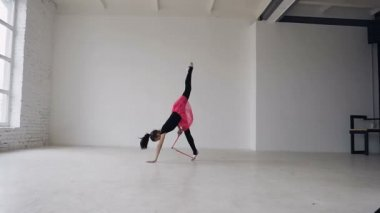 Cute gymnast doing circle with mace on the legs in the white studio on window background. Gymnastics girl dressed black bodysuit and pink skirt