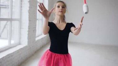Rhythmic beautiful gymnast holding maces it makes acrobatic movements on white background in gymnastic hall. Girl dressed in black body and pink skirt