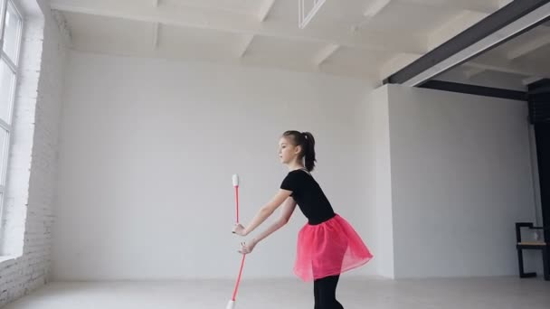 Girl gymnast rotates maces. Girl gymnast with mace in hand revolve around her in sport school in the white background
