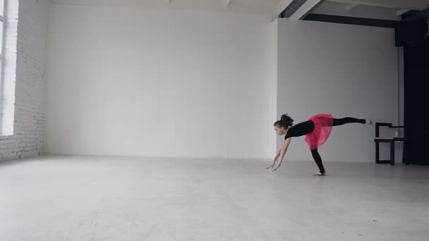 Gymnastics school. Cute gymnast girl performs a backflip with hands in the spacious white ballroom. Flexible girl doing two acrobatic flip. Girl dressed in black bodysuit and pink skirt