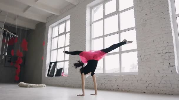 Gymnastics school. Cute gymnast girl performs a back flips with hands in the spacious white ballroom on windows background. Flexible girl doing five acrobatic back flips. Girl dressed in black