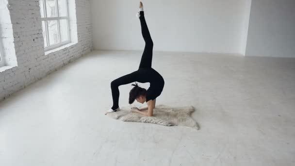 Jóga - gymnastika dívka, aby trénink sportovní škole v bílém pozadí u velkých oken. Pružnost LTV. Mladí fit dospívající dívka se táhnoucí se v tělocvičně. Dívka