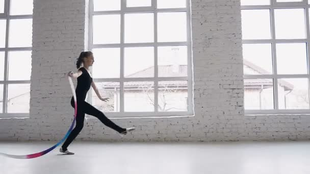 Training of rhythmic gymnastics - teenage girl performs gymnastics exercise with a colored ribbon at white studio or gymnastics school on background big windows. Slim ballerina dressed in black body