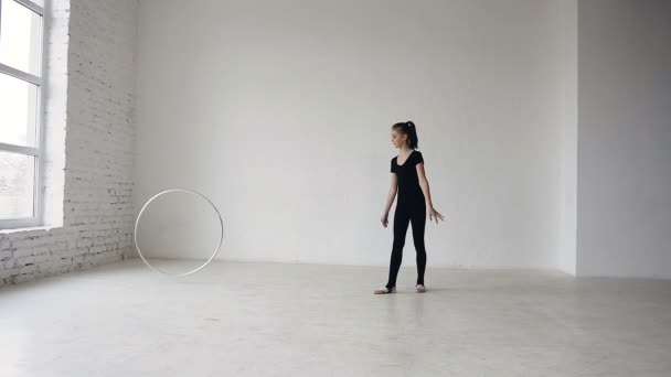 Girl trains with a gymnastic hoop. Rhythmic gymnastics: Blonde girl training a gymnastics exercise with a hoop at gymnastics school at white background