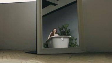 Jong meisje Neem bad vol schuim in de badkamer. Schakelaar muziek ...