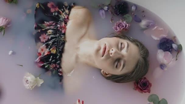 Atraktivní dívka v lázni s mlékem a voňavé poupata květin. Lázeňské procedury omlazení pleti. Svůdná žena ve Spa salonu. Docela sexy mladá žena relaxaci ve vířivce s barevnými poupata květin