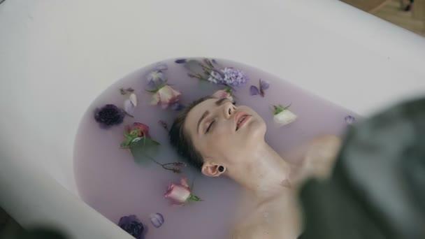 Atraktivní mladá žena v lázni s mlékem a voňavé květy, pupeny. Lázeňské procedury omlazení pleti. Docela sexy mladá žena relaxační v bílé vaně s teplým mlékem a barevná poupata