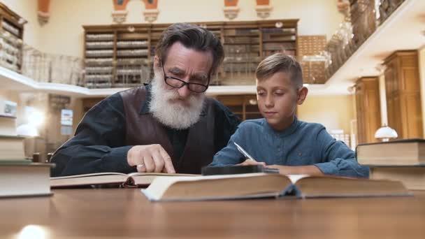 Frontansicht des blonden 12-jährigen Enkels, der zusammen mit seinem älteren intelligenten Opa in der Bibliothek ein Buch liest