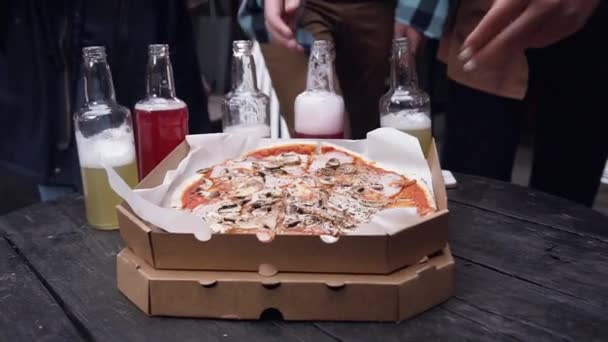 Human hands taking pieces slices of hot tasty italian pizza from open box at party. Catering. Friends having fun enjoying eating and low alcohol drinks hanging out together