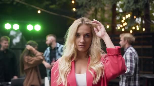 Close up of beautiful blond girl with long hair and blue eyes posing to the camera while her friends dancing in light of colored lamps on evening party