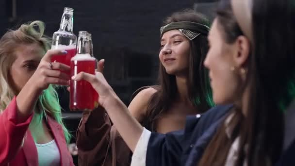 Close-up of happy young female friends having fun together drinking beer and clinking glasses on party at summer evening
