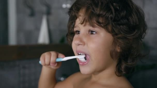 Close view of lovely responsible little boy which cleaning his teeth in the bathroom