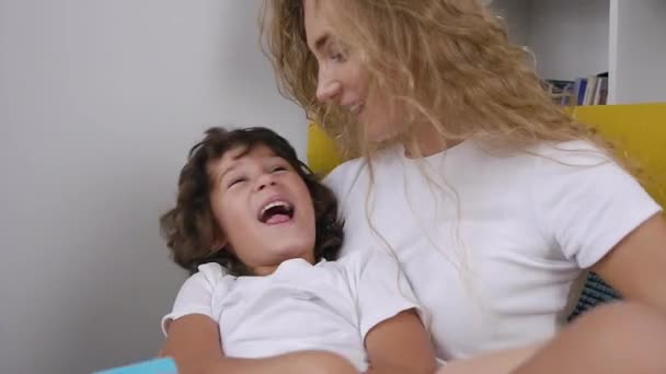 Smiling stunning blond mother tickling her cheerful 5-aged son sitting in the chair during reading book