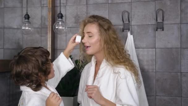 Atraktivní portrét usmívající se krásné maminky a jejího syna, který se baví s krémem na péči o pleť v koupelně