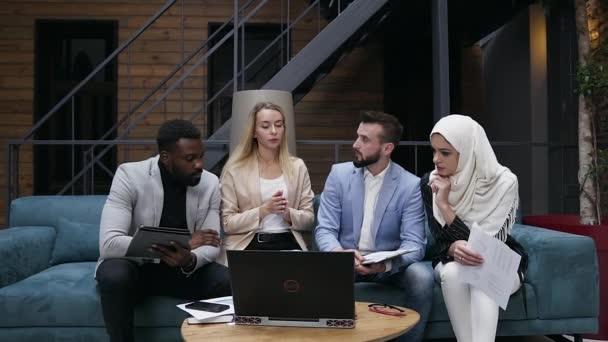 lächelnde sympathische multiethnische männliche und weibliche Geschäftskollegen, die auf der bequemen Couch im modernen Büro sitzen und die Besonderheiten ihres gemeinsamen Projekts besprechen