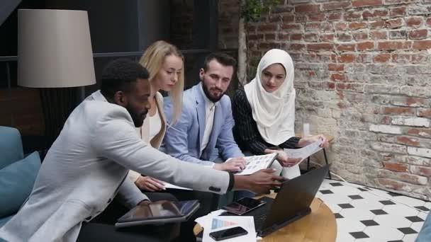 Příjemně dobře vypadající zkušený mladý multiraciální byznys lidí mužů a žen, kteří spolupracují v moderní kancelářské místnosti