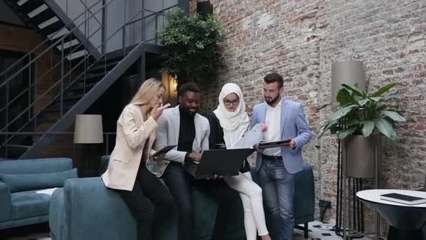 Atraktivní portrét multietnických cílevědomých mladých podnikatelek a podnikatelek, které se opírají o pohovku v moderní kanceláři a diskutují o společném projektu