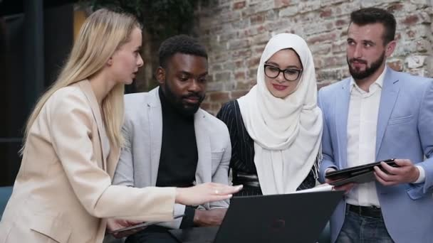 Front view of four concentrated multiracial business colleagues which watching on the computers screen and talking about their joint work in the trendy new office