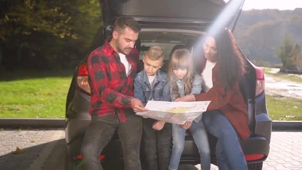 Sympatický usměvavý muž a žena s jejich krásné děti sedí v kufru a dívá se na mapě určit trasu společné rodinné auto výlet