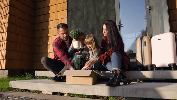 Atraktivní šťastná radostná rodina sedící na schodech a vylézající ze skříňky zelené rostliny v den stěhování