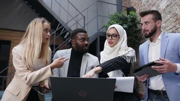 Brainstorm, four multi-ethnic business people uses laptop and computer tablet while discussing financial deal at modern boardroom