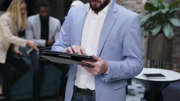 Portrétní snímek profesionálního bělošského podnikatele, který si dělá poznámky do tabletu počítačové aplikace na pozadí svých spolupracovníků v moderní kanceláři. Dolly shot