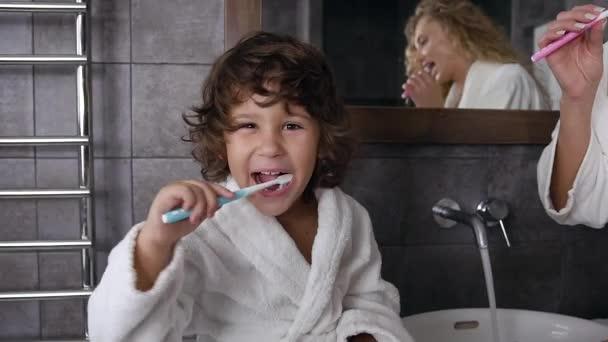 Veselý chlapeček s kudrnatými vlasy v bílém kabátě si čistí zuby zubní pastou a kartáčkem na zuby u mámy v koupelně. Dolly shot