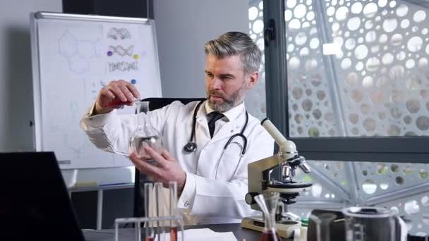Vážený šedovlasý lékař provádí chemické experimenty s kapalinami ve zkumavce a baňce v lékařské laboratoři
