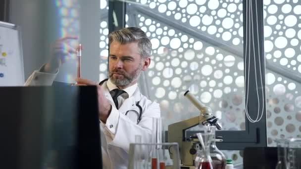 Přední pohled na dobře vypadajícího slušného lékaře v bílých šatech, který provádí experimenty s chemickou kapalinou ve zkumavce a zapisuje výsledky do lékařské zprávy