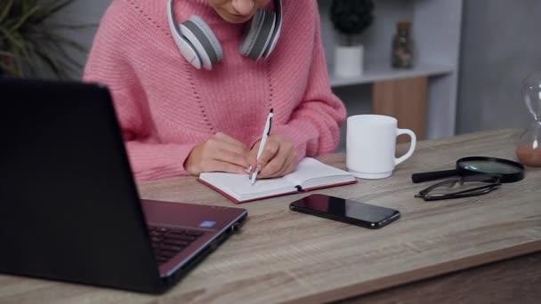 Zblízka pohled na půvabné mladé ženy v růžovém svetru, který píše něco po levé ruce