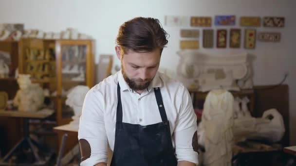 attraktive moderne bärtige Meister in weißem Hemd und Schürze stehen mit gefalteten Händen und schauen in die Kamera mit ernstem Gesicht