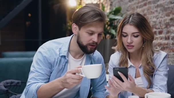 Krásný portrét pohledný vousatý chlap a okouzlující blond žena s dlouhými vlnitými vlasy, které sedí spolu v hotelu a pití čaje při použití telefonu