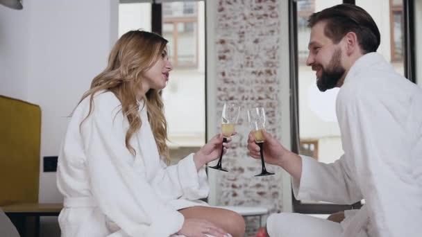 charmant lächelndes glückliches verliebtes Paar in Bademänteln auf dem Bett sitzend und Sekt in ihrem Hotelzimmer trinkend
