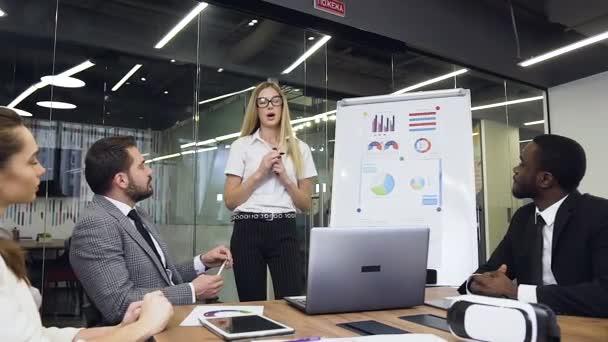 sympathische selbstbewusste moderne Geschäftsfrau, die die Geschäftsstrategie der gemeinsamen Arbeit für die hochqualifizierten multiethnischen ernsthaften Geschäftsleute erklärt