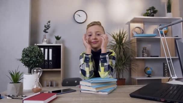 Atraktivní portrét pohledného teen školáka, který se dívá do kamery s pěkným úsměvem a ukazující znamení OK