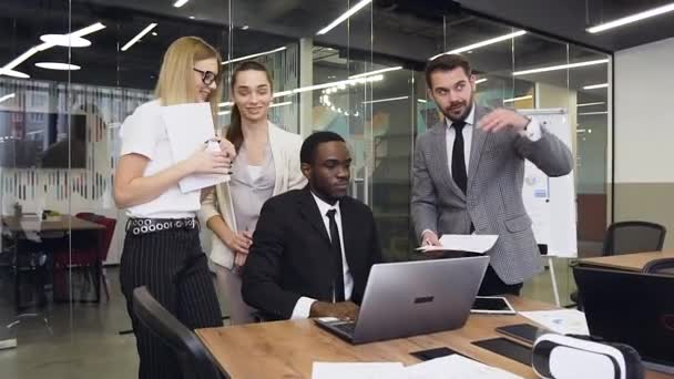 Dobře vypadající spokojená multietnická skupina podnikatelů, kteří společně diskutují o dalších akcích týkajících se společného podnikatelského projektu