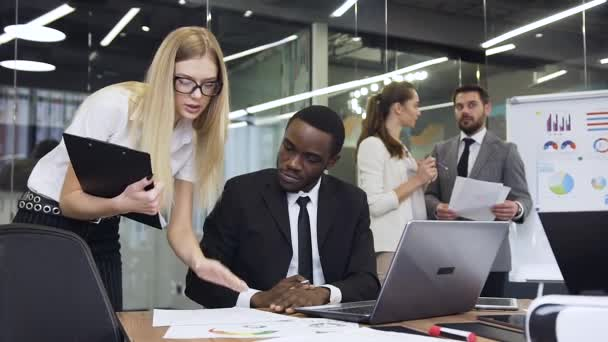 Atraktivní vznešený vousatý podnikatel hovořící se svou zkušenou obchodní kolegyní, zatímco další mnohonárodnostní obchodní kolegové revidují důležité dokumenty