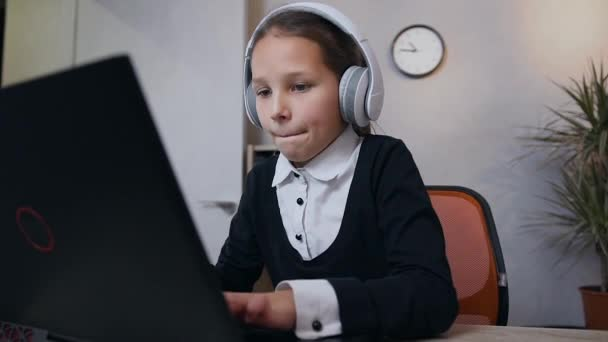 Slow motion of beautiful happy teen girl in headphones which playing video game on computer and raised her hands up after victory
