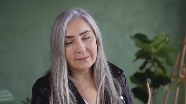 Smiling attractive confident gray haired woman in stylish jacket posing on camera while putting on her eyeglasses