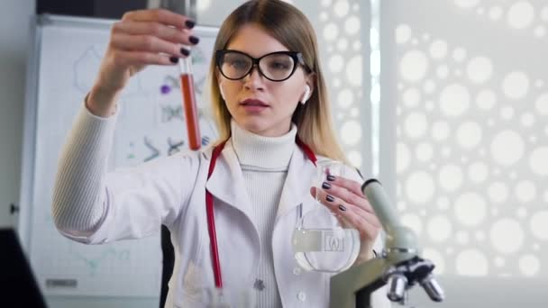 Portrait of serious female doctor in glasses wich uses test tubes with liguid and doing medical researchh