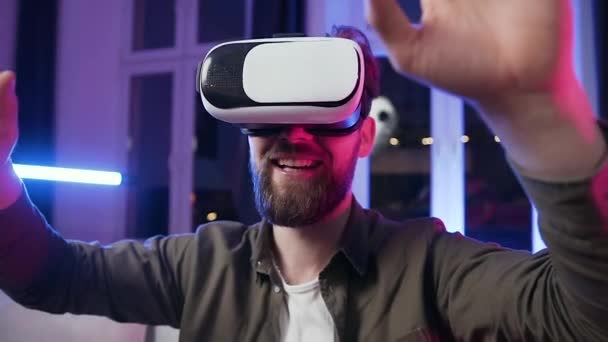 Close up of good-natured happy joyful bearded guy which moving his hands on virtual screen using special 3d glasses