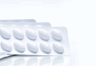 Macro shot of pills in white blister pack for light resistance packaging isolated on white background. Medicine for treatment dyslipidemia. Lipid lowering tablets pills. Statins : Hyperlipidemia.