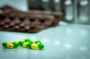 Green, yellow tramadol capsule pills on blurred blister pack background with copy space. Cancer pain management. Opioid analgesics. Drug abuse in teenage in Thailand.