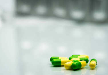 Green, yellow tramadol capsule pills on blurred silver blister pack background with copy space. Cancer pain management. Opioid analgesics. Drug abuse in teenage